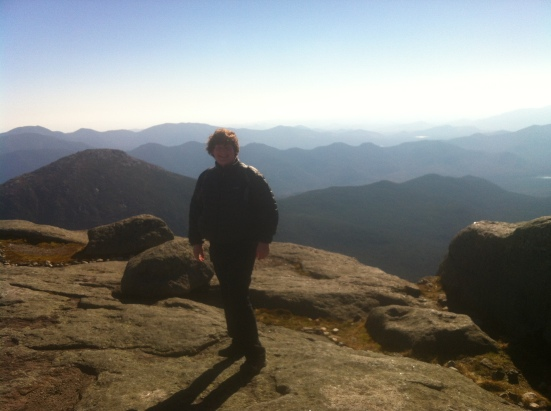 Braving the wind on the 5,344 foot summit of Mt Marcy, highest peak in the Adirondacks